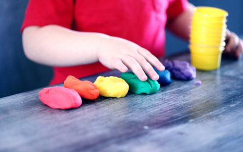 Child playing with six colours of play dough. Child's face is not in view.