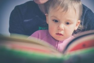 Toddler reading a book with their parent. Their parent is out of view and behind them.