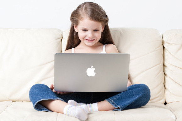 Young girl sitting on a couch looking at a laptop that is on her lap, she is smiling