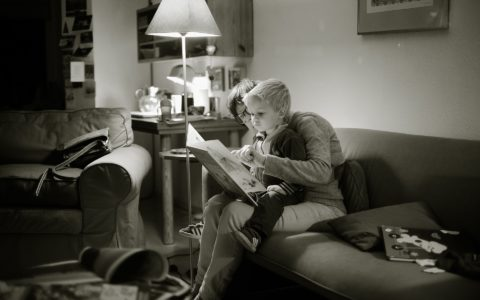 Black and white photo of a child and an adult reading a picture book together. Child is sitting in adult's lap.